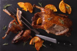 Cutting the roast duck and oranges on a slate board horizontal