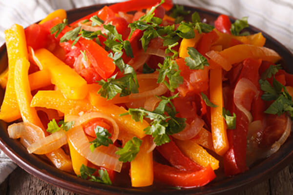 Stewed peppers with tomatoes and onions close up horizontal