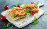 Homemade grilled toast with smoked salmon, rucola, tomatoes on white board healthy breakfast